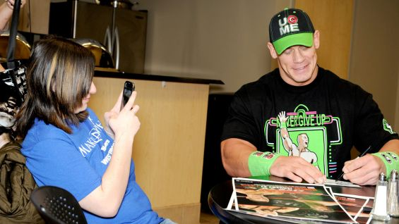 The 16-year-old takes photos as Cena signs her WWE memorabilia.