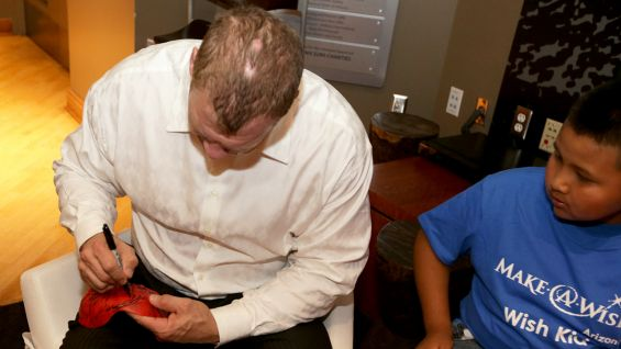 Kane autographs a replica of his mask for Kevin.