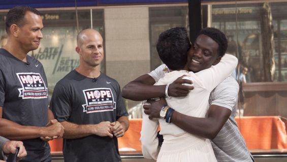 Co-host Hall hugs Singleton, who will throw out the first pitch at the Yankees game.