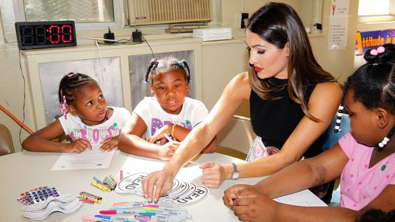 After reading with the children, Nikki Bella makes crafts with the kids.