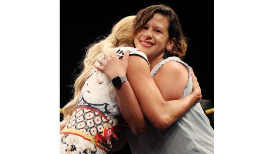 Dana presents a championship to Angelica Frey, breast cancer survivor.