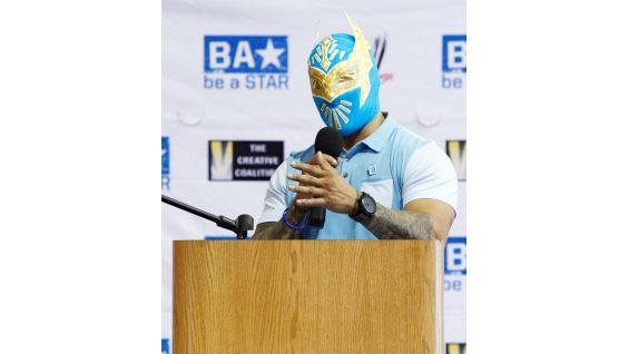 Sin Cara speaks to the predominantly Latino crowd by alternating in both English and Spanish to relate to the bilingual attendees.