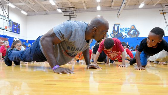 Titus O'Neil helps a young fan perfect his push-up form.
