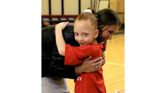 WWE Chief Brand Officer Stephanie McMahon gives a hug to one of the young athletes.