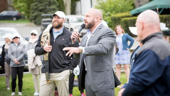 Keisel clutches the WWE Championship as Triple H talks.