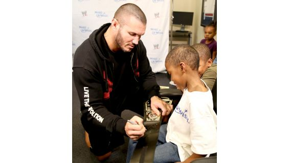 Orton signs autographs for the young WWE fan.