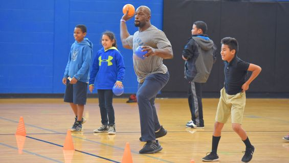 Titus O'Neil steps up to lead a team of kids in a game of dodgeball.