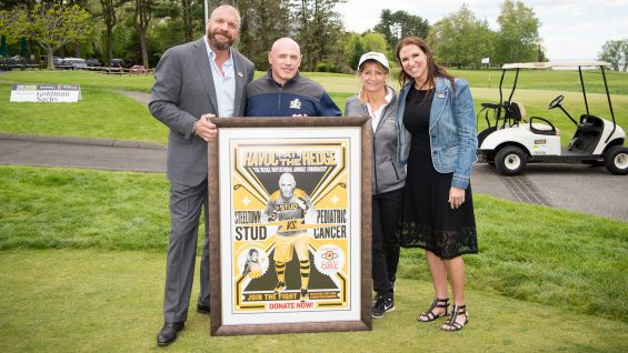 Rob and Cindy Citrone take a picture with the Stephanie, Triple H, and the event artwork. The Citrone's are the founders of Discovery Capital Management and minority owners of the Pittsburgh Steelers.