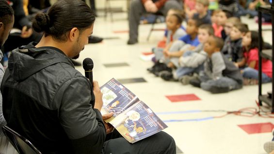 Roman Reigns reads a story to the children.