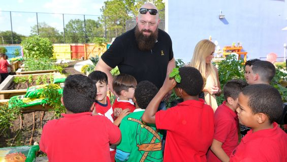 Big Show and Dana Warrior take a tour of the Englewood Neighborhood Center's garden.