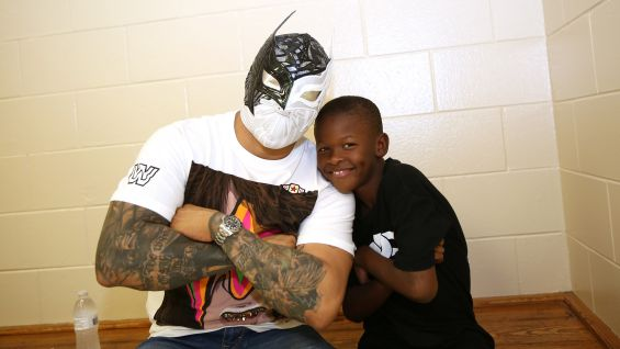 Sin Cara strikes a pose with a fan at Orlando's Smith Community Center.