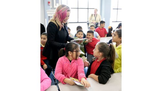 "Natalya passes out copies of ""Not Your Typical Dragon"" to the students."