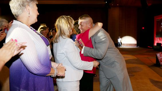 Cena greets breast cancer survivors in the front row of the event.