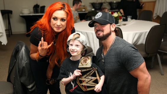 Becky Lynch and AJ Styles pose with a young fan at a reception to celebrate the new partnership before Raw.