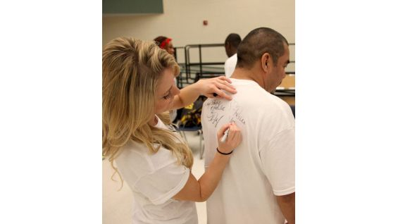 The basketball game's announcer, Renee Young, signs an autograph for an athlete.