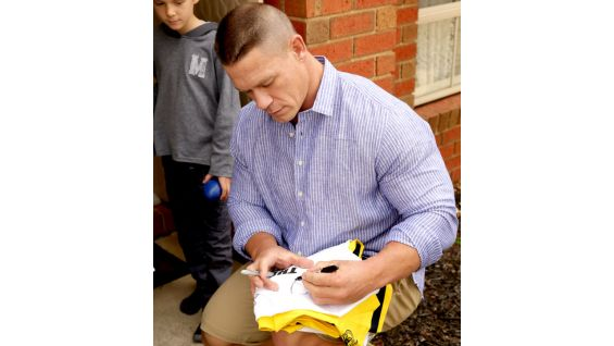 The WWE Champion signs autographs for Rhys, who is 10 years old.
