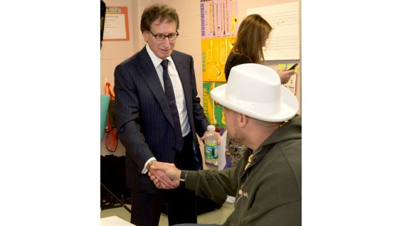 Dr. Bob Goldman of The Rotary Club of Stamford shakes hands with The Funkasaurus.