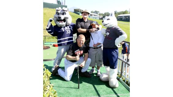 The Hall of Famers pose with a Special Olympian and Yale's mascot, Handsome Dan the bulldog, and UCONN's Jonathan the husky.