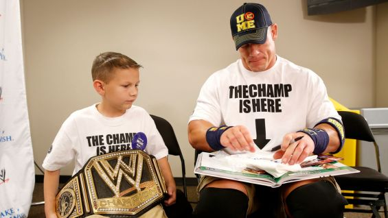 Cena signs autographs and checks out Nicholas' scrapbook.