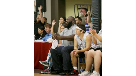 The World's Strongest Man cheers on his players from his courtside seat.