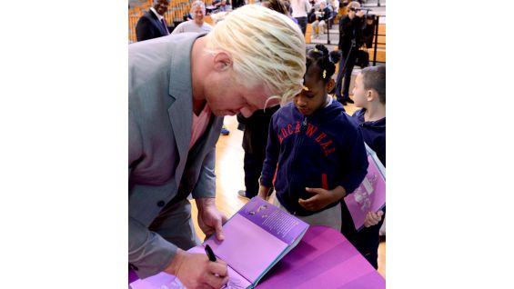 Ziggler autographs the childrens' books.