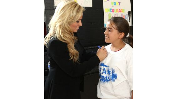 Natalya signs an autograph for an excited youngster.