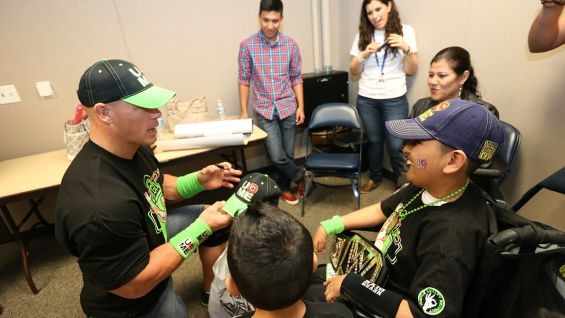 Cena signs autographs for the Circle of Champions honoree.
