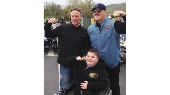 Sgt. Slaughter joins Mike Kennedy, Harley-Davidson's National Vice President of Sales, and Bryson Foster, MDA's National Goodwill Ambassador, 2012 to 2013.