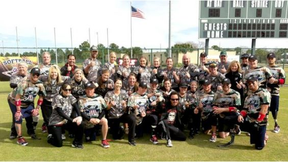 "Jimmy Hart poses with players from the ""God and Country Weekend"" charity softball game."