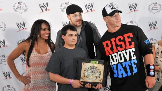 The Superstars hand out special WWE Circle of Champions Certificates plaques to each Wish kid.