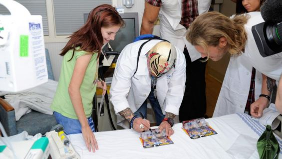 Mysterio and Edge sign action figures for the patients.