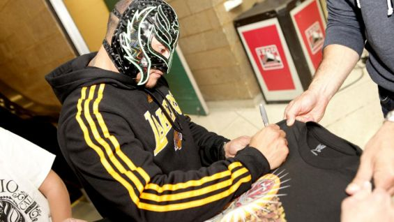 The masked Superstar signs a new Mysterio shirt for one of his biggest fans.