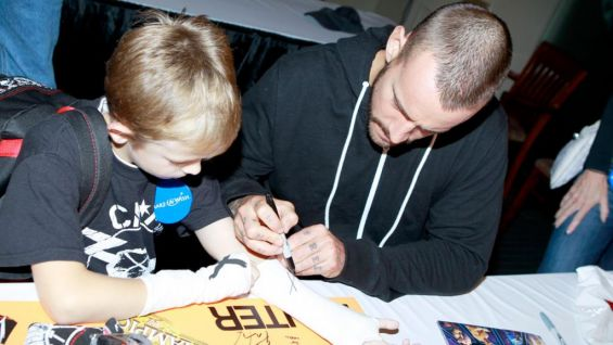 Hunter has the WWE Champion sign the special poster he created for his wish.
