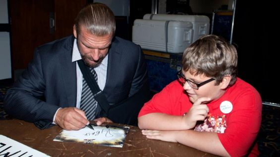 The WWE COO signs autographs for the 8-year-old.