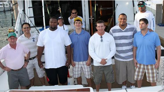 DiBiase poses with some members of the Miami Dolphins.