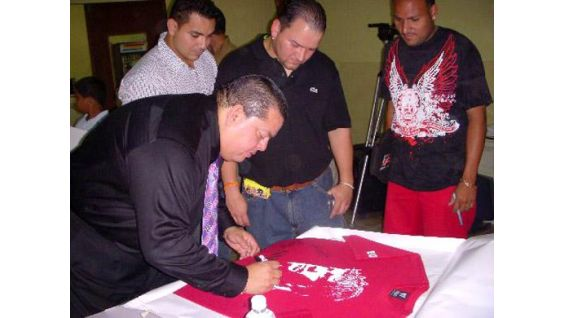 Hugo Savinovich signs an Eddie Guerrero T-shirt for his listeners.