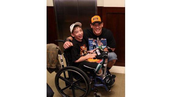 Brandon Elliot, 13, of Cranbrook, British Columbia, Canada, smiles with Cena.