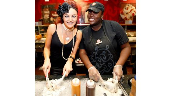 Maria makes an ice cream creation with a Cold Stone employee.