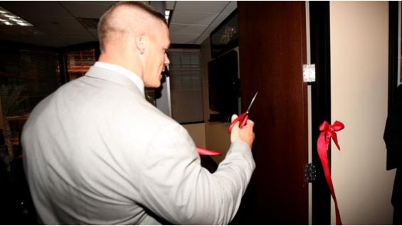 The leader of the Cenation cuts the ribbon to the new WWE conference room.
