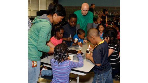 The WWE employee volunteers help the children plant seeds.