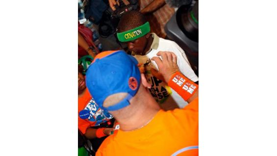Cena signs Omari's brother's Cup with a Cause T-shirt.