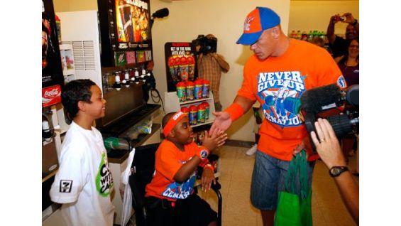 Cena meets Omari, 10, center, and Caleb, 8, of the Make-A-Wish Foundation.