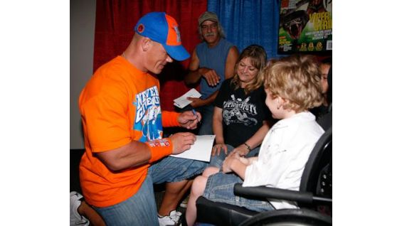 Cena signs an autograph for the Circle of Champions honoree.