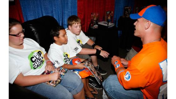 Cena also talks to Caleb, 8, center, from the Make-A-Wish Foundation.