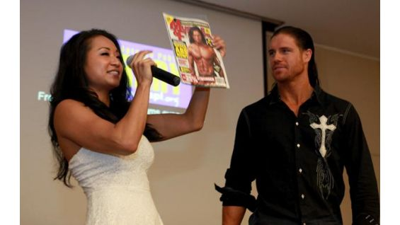 "Gail holds up Morrison's cover issue of ""Muscle & Fitness"" for all to see."