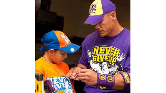 Cena signs one of his signature pendants for Seth Hawkins.