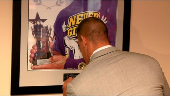 Cena leaves his mark on the WWE conference room at Make-A-Wish Foundation headquarters.