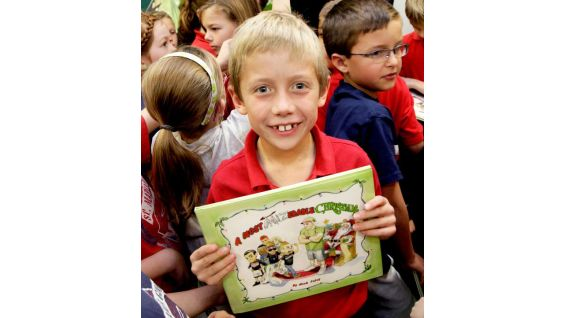 "A proud first-grader at Saint Maria Goretti holds his copy of ""A Most Mizerable Christmas."""