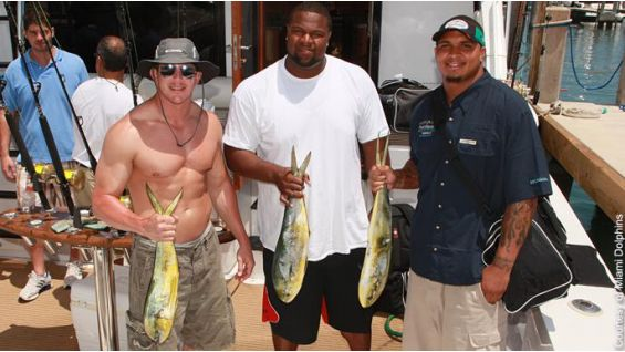Vern Carey, Mike Pouncey and DiBiase show off the catch of the day.