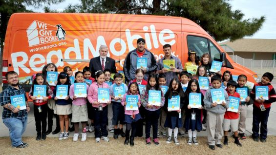 The Superstars and students pose with the books they received from the WeGiveBooks.org ReadMobile.